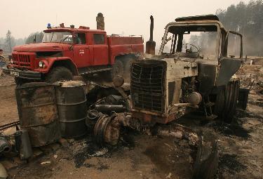 Un trattore carbonizzato da un incendio in Russia (Foto Ansa)