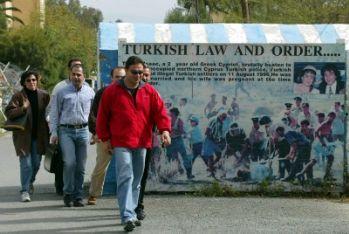 Turchi ciprioti davanti a un manifesto per un greco cipriota ucciso