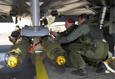 Soldati francesi controllano un jet Mirage 2000 prima di una missione (Foto Ansa)