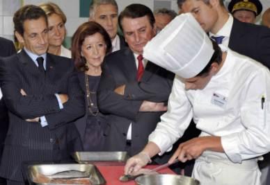 Il Presidente francese Nicolas Sarkozy osserva un cuoco al lavoro (Foto Ansa)