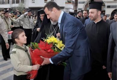Il presidente siriano Assad partecipa a una festa cristiana (Ansa)