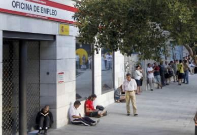 Una coda davanti a un ufficio pubblico per l'impiego di Madrid (Foto Ansa)
