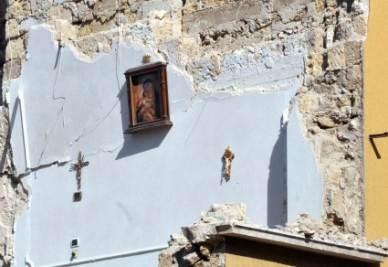 Un quadro con la Madonna e due crocifissi, rimasti alla parete di una camera da letto nella palazzina crollata a Barletta (Foto Ansa)