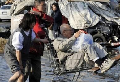 Alcuni giapponesi in cerca di un riparo dopo lo Tsunami (Foto Ansa)