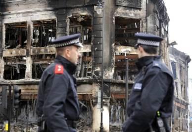 Due poliziotti inglesi davanti a un edificio bruciato (Foto: ANSA)