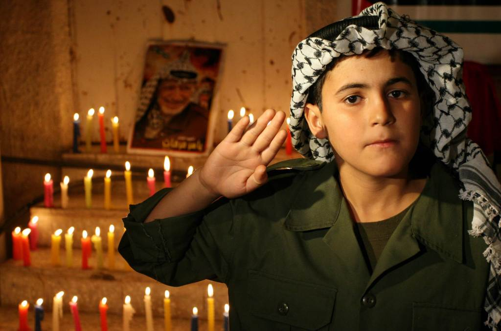 Palestinian boy with a photo of Arafat  (Infophoto)