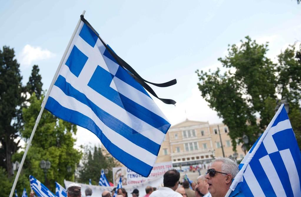 Le bandiere della Grecia sventolano a lutto (Foto: Infophoto)