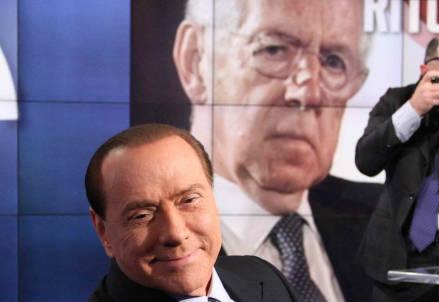 Silvio Berlusconi, leader del Popolo della Libertà e sullo sfondo un'immagine di Mario Monti, attuale presidente del Consiglio dei Ministri