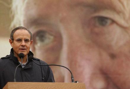 Julián Carrón con il volto di Luigi Giussani sullo sfondo (Infophoto)