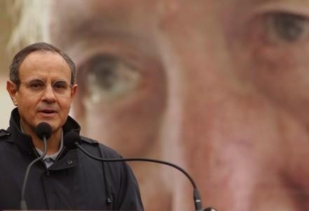 Don Julian Carron. Sullo sfondo, una delle ultime immagini di don Giussani