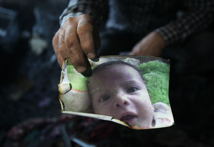 Un uomo mostra la foto di Ali Saad Dawabsheh (InfoPhoto)