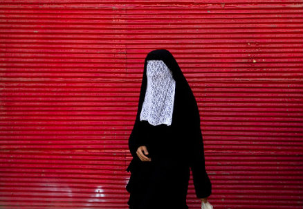 Una donna con il burqa (Infophoto)