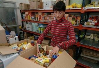 Una volontaria riempie un pacco per i poveri