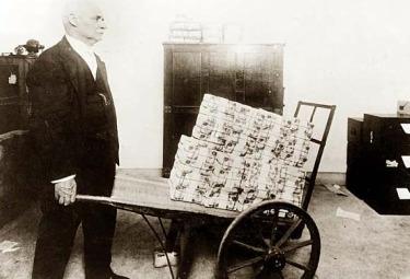 Un uomo a Weimar trasporta banconote per fare spese con una carriola (1923)