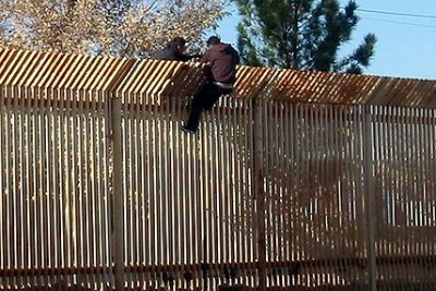 Two men scaling the US-Mexico border  (US Navy photo)
