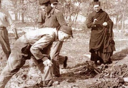 Un prete benedice i resti di vittime infoibate (Immagine dal web)
