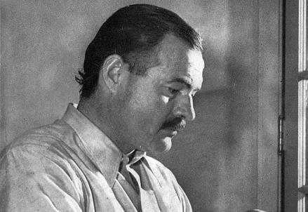 Ernest Hemingway (1899-1961) al suo tavolo di lavoro (Foto da Wikipedia)