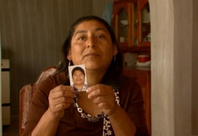 Clemencia holds up a photo of her husband, Josefat, who disappeared in the Sonoran Desert. Photo courtesy of www.theundocumented.co