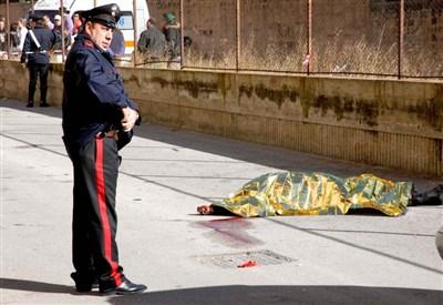 Un carabiniere accanto a un corpo (Foto: Infophoto)