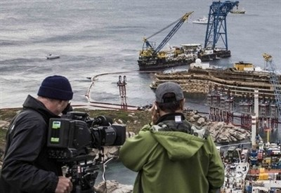 Cameramen verso la Costa Concordia (Infophoto)