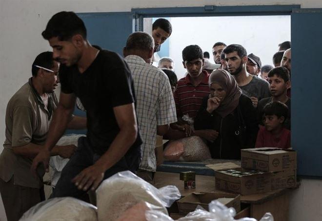 Palestinesi ricevono aiuti Onu nel campo di Jabalia, Gaza (LaPresse)