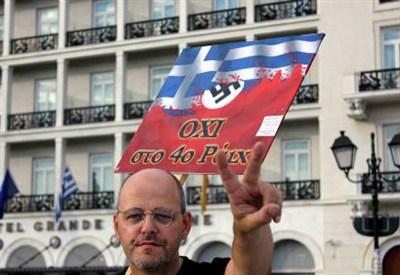 """Un manifestante davanti alla scritta """"No al Quarto Reich"""""""