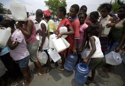 Haitiani in coda per l'acqua, a tre mesi dal terremoto del 2010 (Infophoto)