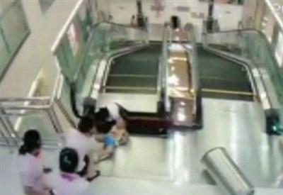 Una immagine della donna mentre cade nel buco della scala mobile