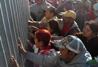 Migranti messicani al confine con gli Usa (Infophoto)
