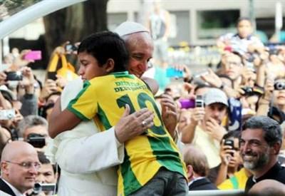 Papa Francesco abbraccia un bimbo brasiliano (Infophoto)