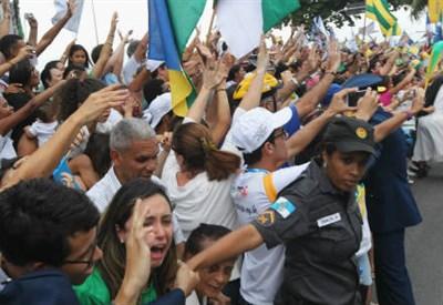 Giovani accolgono Francesco in Brasile (Infophoto)