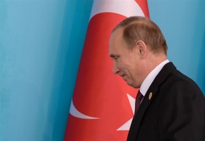 Vladimir Putin e sullo sfondo una bandiera turca (Infophoto)
