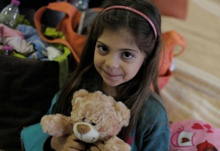Bambina sfollata con il suo orsacchiotto (LaPresse)